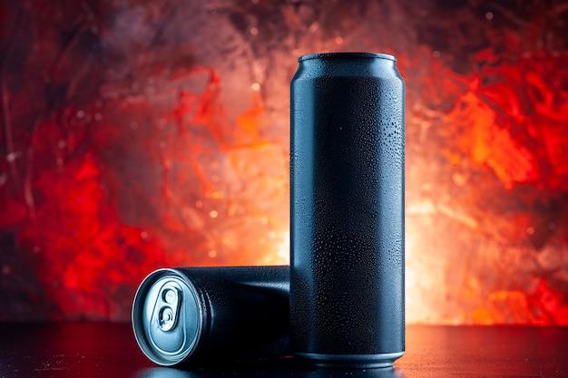 Bevanda energetica vista frontale in lattine sull'oscurità della foto dell'alcool della bevanda rossa