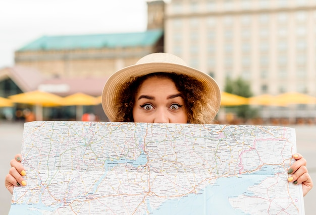 Front view enthusiast woman traveling alone with a map