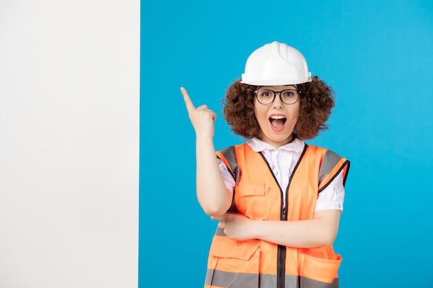 Вид спереди взволнованная женщина-строитель в униформе на синем
