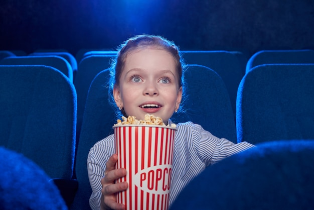 Front view of excited girl eating cheese popcorn and watching amazing film in cinema.
