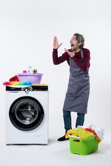 Вид спереди возбужденный домработница, глядя вверх, стоя возле корзины для белья стиральной машины на белом фоне