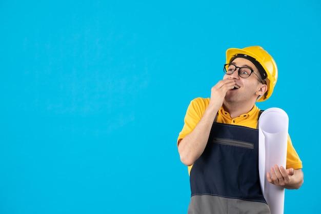 Вид спереди взволнованный мужчина-строитель в униформе с бумажным планом, смотрящим выше на синем