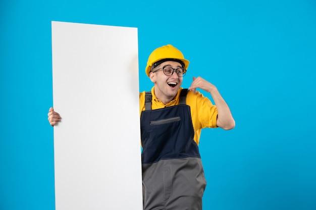 Вид спереди взволнованный мужчина-строитель в форме с бумажным планом на синем