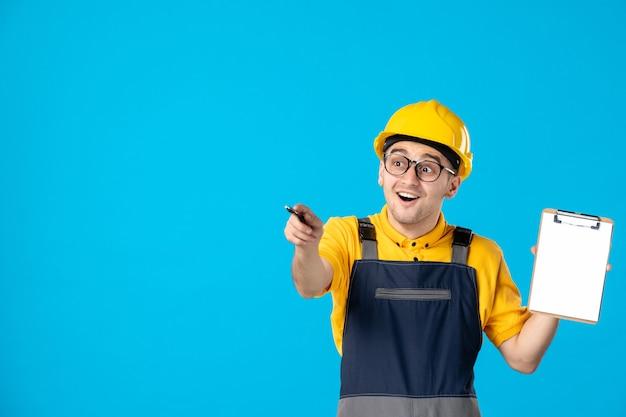 Vista frontale del costruttore maschio eccitato in uniforme e casco con il blocco note su una parete blu