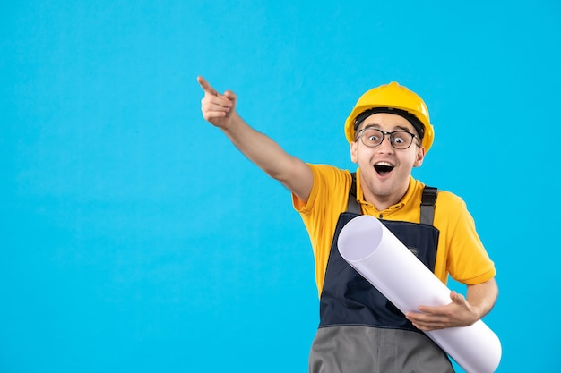 Front view excited male builder in uniform with paper plan on blue