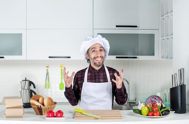 Chef maschio eccitato vista frontale in piedi dietro il tavolo della cucina in cucina