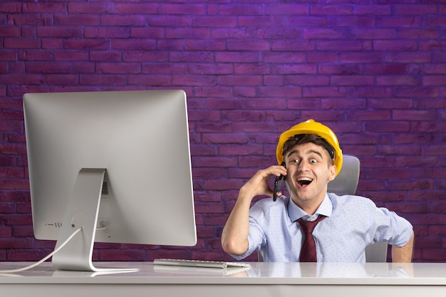 Front view excited male constructor behind office desk talking at phone