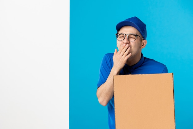 Front view excited male courier in uniform with delivery pizza blue