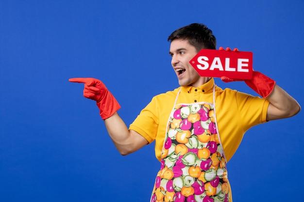 Vista frontale eccitata governante maschio con guanti di scarico con cartello di vendita rosso su spazio blu