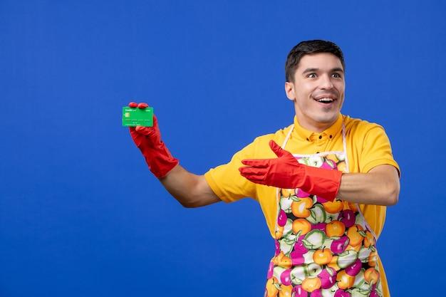파란색 공간에 카드를 들고 빨간색 배수 장갑을 끼고 흥분된 남성 가정부 전면 보기