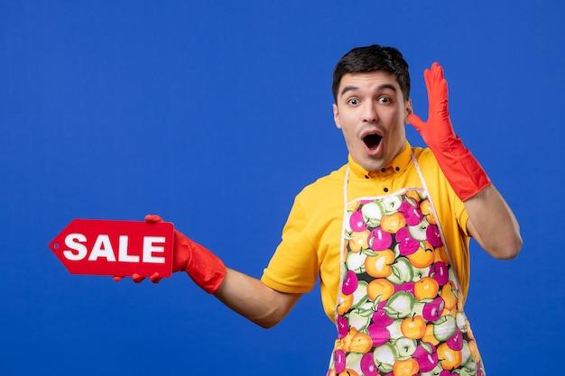 Vista frontale eccitata governante maschio in maglietta gialla con cartello di vendita su spazio blu