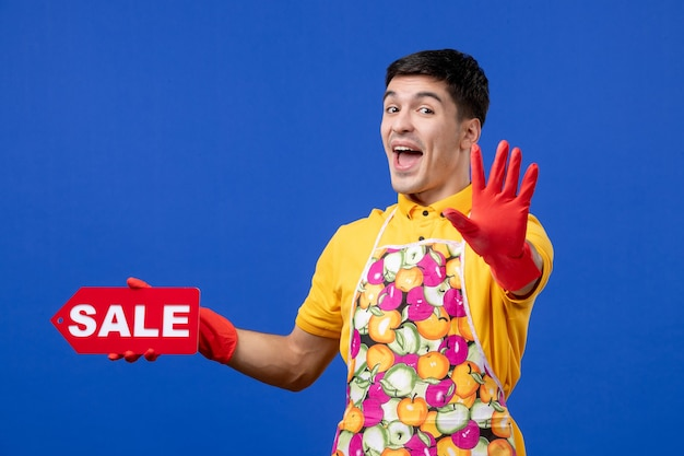 Front view excited male housekeeper in yellow t-shirt holding sale sign making stop sign on blue space