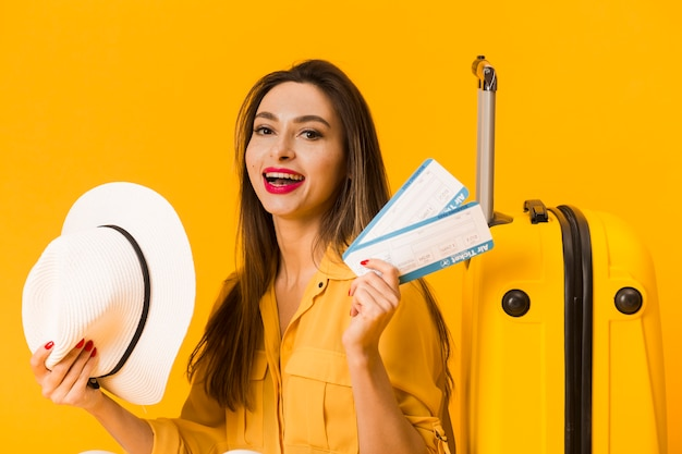 Front view of excited woman holding plane tickets