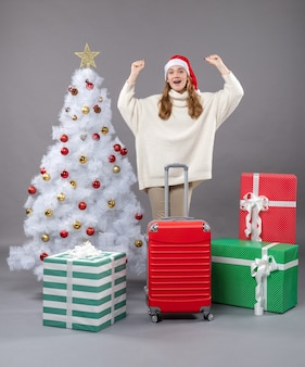 Vista frontale donna eccitata alzando le mani con valigia