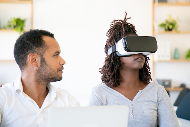 Front view of excited woman testing vr headset with assistant