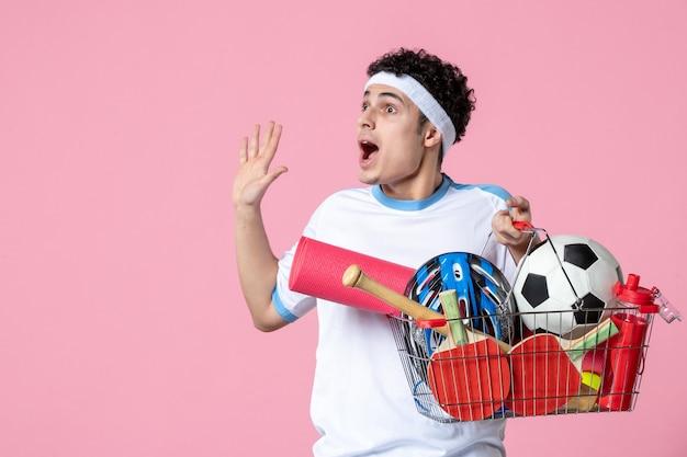 正面図は、スポーツ用品でいっぱいのバスケットとスポーツ服を着た若い男性を興奮させました
