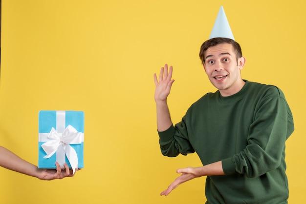 Вид спереди возбужденного молодого человека, показывающего подарок в человеческой руке на желтом