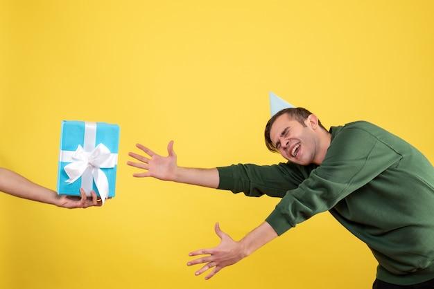Vista frontale eccitato giovane uomo che cerca di catturare il dono in mano umana su giallo
