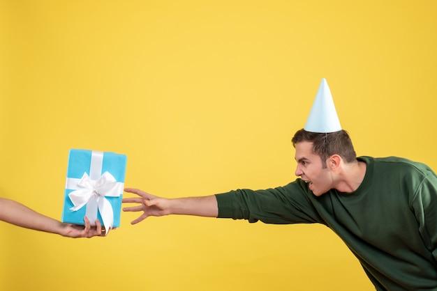 Вид спереди возбужденного молодого человека, пытающегося поймать подарок в человеческой руке на желтом