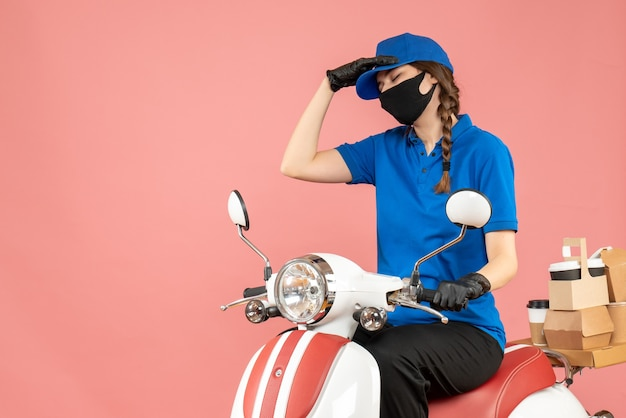 Front view of exhausted courier girl wearing medical mask and gloves sitting on scooter delivering orders on pastel peach background