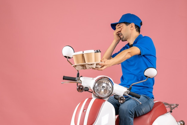 Front view of exhausted courier man wearing hat sitting on scooter on pastel peach background