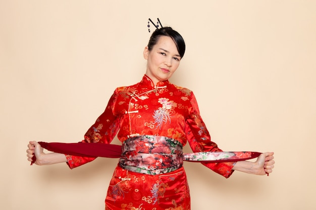 A front view exquisite japanese geisha in traditional red japanese dress posing elegant with designed belt on the cream background ceremony japan