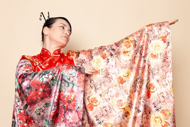A front view exquisite japanese geisha in traditional red japanese dress posing with flower designed tissue elegant on the cream background ceremony japan