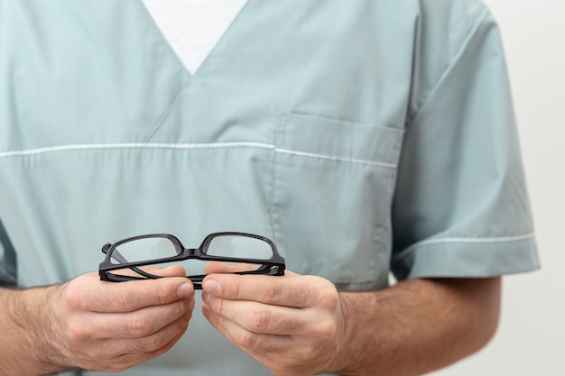 Front view of eye specialist holding pair of glasses in hands