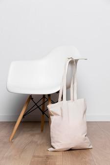 椅子にぶら下がっている正面図の生地のトートバッグ