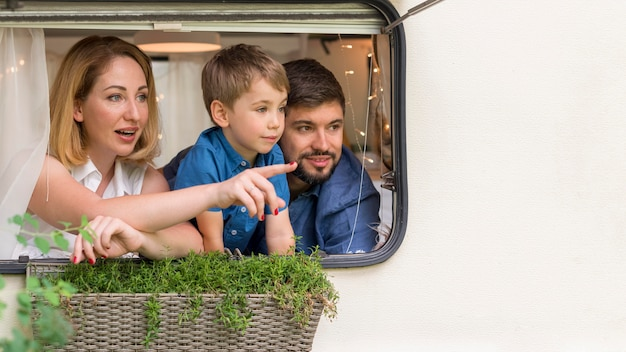 Front view family looking out of a caravan's window with copy space
