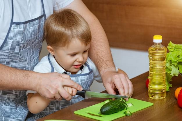正面の父と息子のキッチンでサラダの野菜をカットしました。