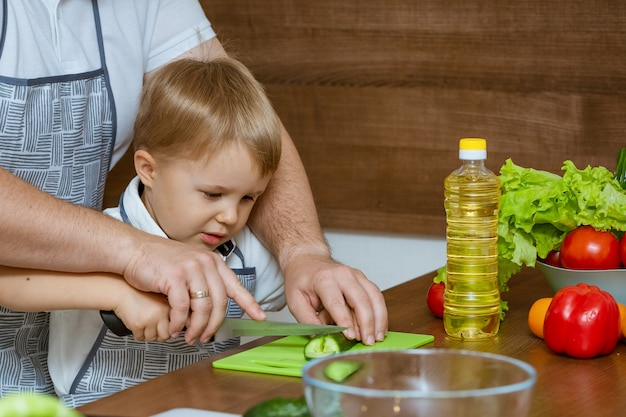 Отец и сын вид спереди в кухне нарезанные овощи для салата.