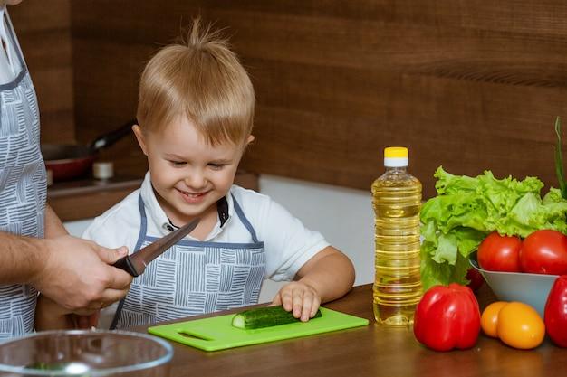 Вид спереди отец и сын на кухне нарезать овощи для салата