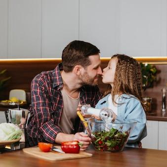 Vista frontale di padre e figlia che vanno a baciarsi mentre preparano il cibo in cucina