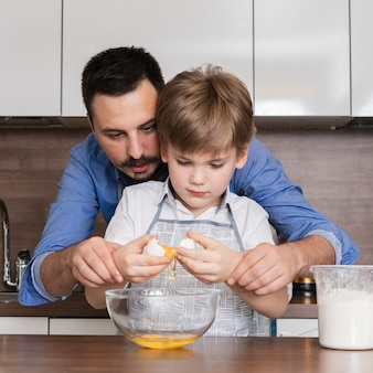 Front view father helping son to crack eggs