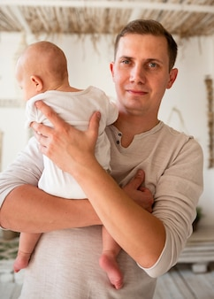 Front view of father holding newborn
