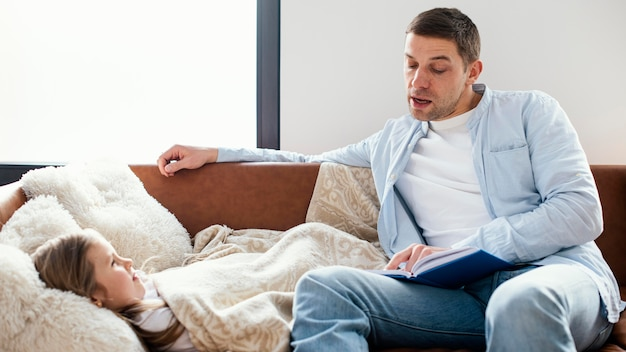 Front view of father reading a story to daughter in bed
