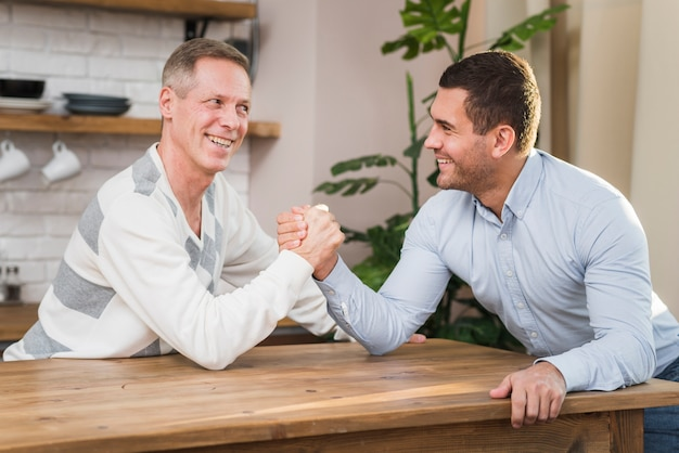 Front view of father and son doing armwrestling