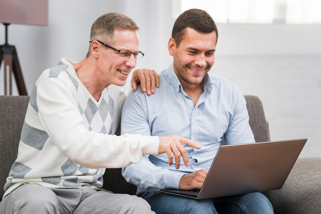 Front view of father and son looking at laptop