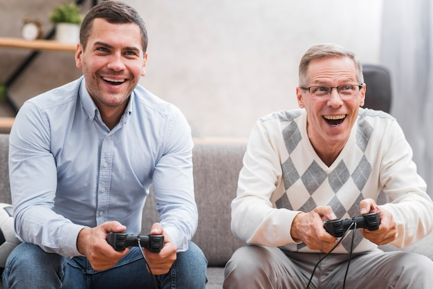 Front view of father and son playing with joystick