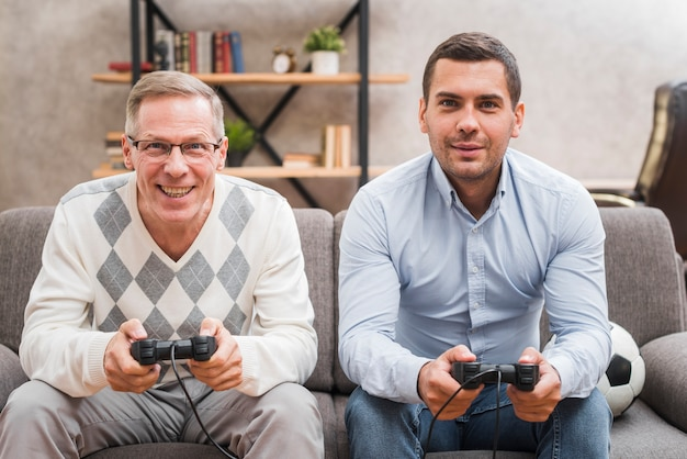 Front view of father and son playing with joysticks