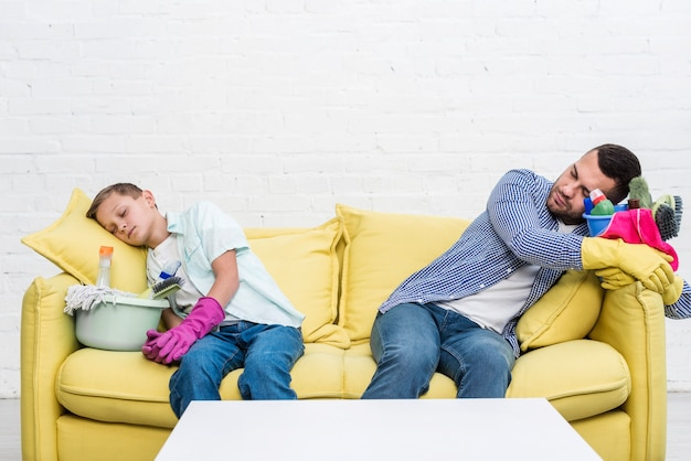 Front view of father and son resting on sofa after cleaning