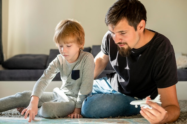 Front view of father and son with map and airplane figurine