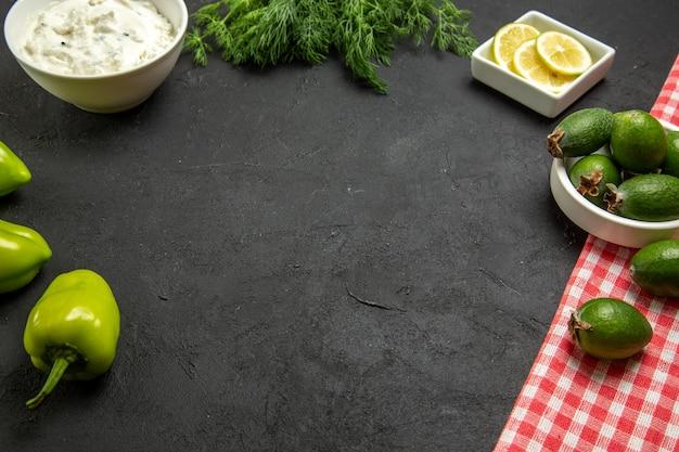 Вид спереди фейхоа и лимон с зеленым болгарским перцем и зеленью на темной поверхности фруктово-овощной муки