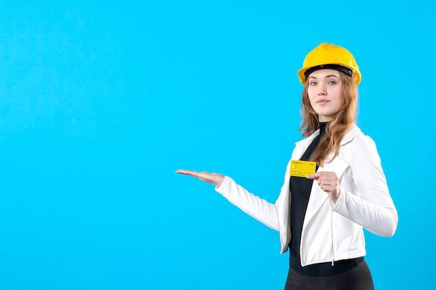 Architetto femminile di vista frontale che tiene carta di credito su blue