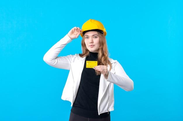 Вид спереди женский архитектор, держащий банковскую карту на синем