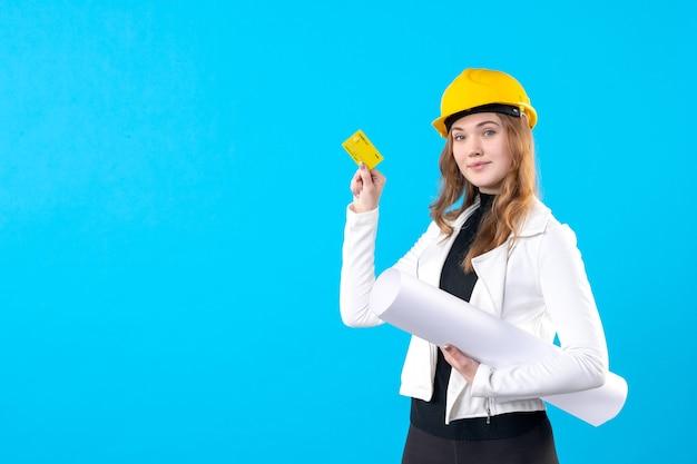 Вид спереди женский архитектор, держащий план и банковскую карту на синем