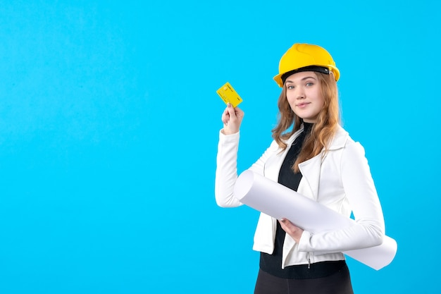 Vista frontale dell'architetto femminile che tiene il piano e la carta bancaria sul blu