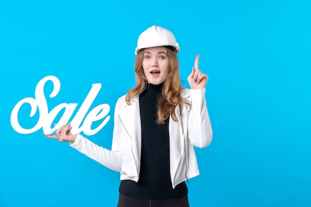 Architetto femminile di vista frontale che tiene la vendita di scrittura su casa di costruzione di lavoro piatto di architettura del costruttore di operaio blu