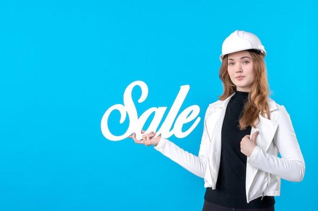 Architetto femminile di vista frontale che tiene la scrittura bianca di vendita sul blu